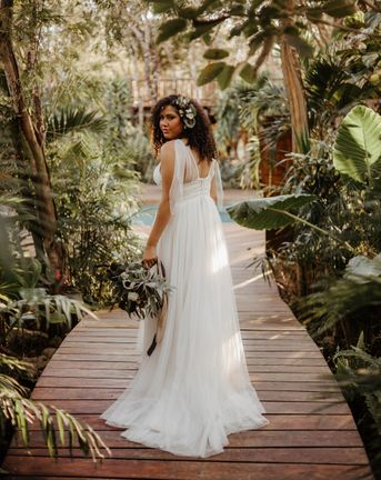 Tulum destination wedding with tropical plants a bride in a floaty dress with naturally curly hair