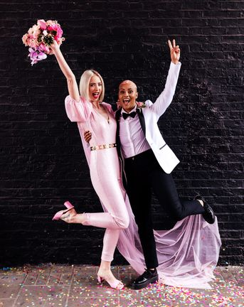 Alternative wedding inspiration with two brides in a pink jumpsuit and white tuxedo jacket