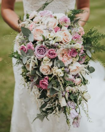 pink lilac and white bouquet filled with roses and lisianthus for bride wearing Christina Wu dress