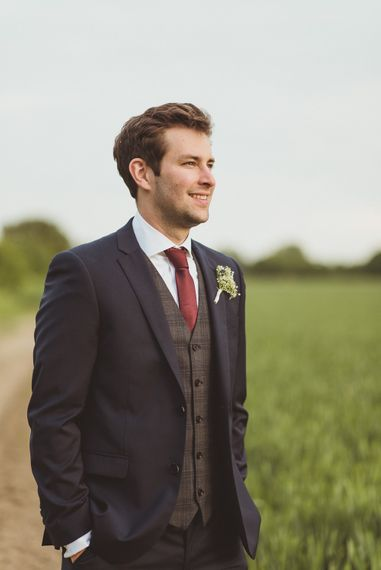 Groom in Navy DKNY Suit from Moss Bros