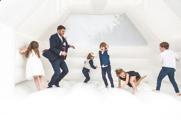 Groom & Miniature Wedding Guests on the Bouncy Castle