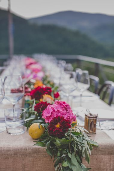 Outdoor Wedding Ceremony in Tuscany With Bright Florals And Rustic Wooden Seating