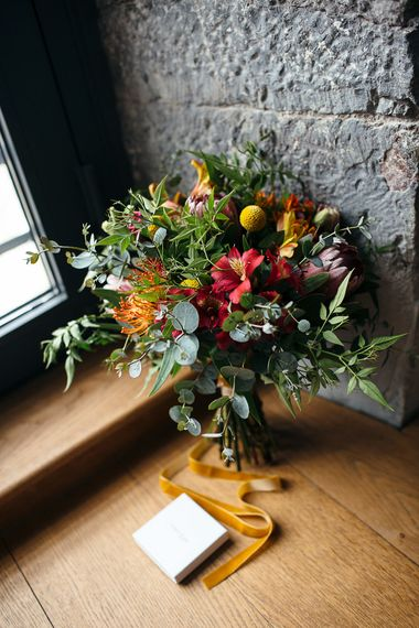 Colourful Red, Orange & Yellow Bouquet with Proteas   Relaxed Industrial Wedding at Ocean Studios, Plymouth   Freckle Photography