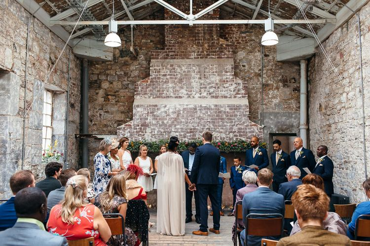 Wedding Ceremony   Bride in Bespoke Ailsa Monroe Jumpsuit & Cape   Groom in Next Navy Wool Suit   Relaxed Industrial Wedding at Ocean Studios, Plymouth   Freckle Photography