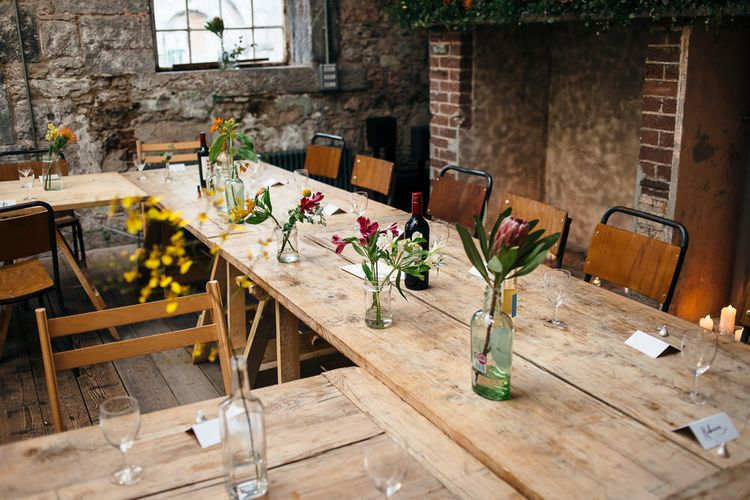 Trestle Tables with Flower Stems in Bottles     Relaxed Industrial Wedding at Ocean Studios, Plymouth   Freckle Photography
