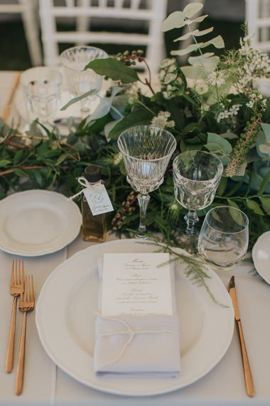 Elegant Place Setting with Gold Flatware & Greenery Table Runner