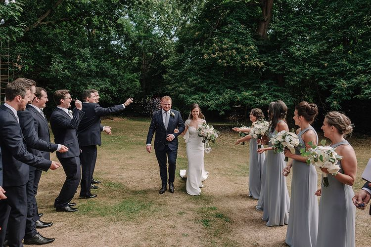 Confetti Exit | Bride in Lace Pronovias Bridal Gown | Groom in Thom Sweeney Suit | White and Silver English Country Garden At Home Marquee Wedding | Jason Mark Harris Photography