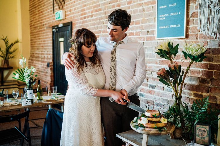 Cutting the Cake | Bride in Lucy Can't Dance Jungle Fever Bridal Gown | Groom in Brown Next Suit | Bohemian Wedding at Woodfarm Barn, Suffolk | The Steed Photography