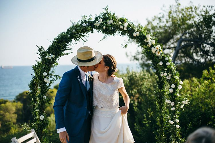 Bride in Verónica Miranda Bridal Separates & Groom in Navy Suit by The Fitters Under Floral Arch