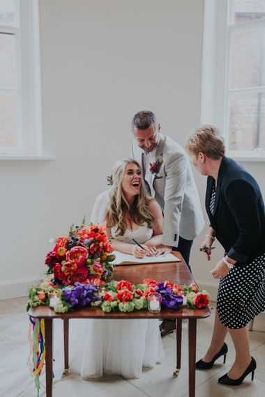 Signing The Register // Colourful Spring Wedding At Iscoyd Park With Coral Charm Peonies And Bride In Pronovias Images From Kate Gray Photography