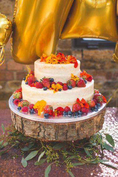 Semi Naked Wedding Cake Laden With Fruit on Rustic Tree Slice Cake Stand   Kirsty Mackenzie Photography   Insta Wedding Films