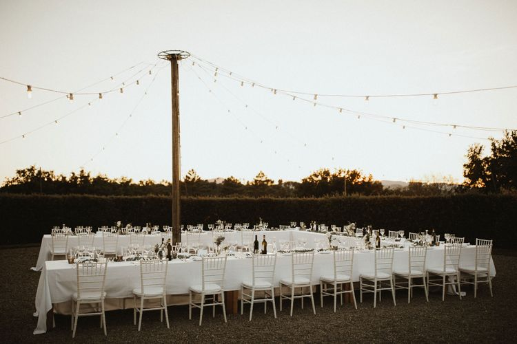 Outdoor Dining At Destination Wedding With Festoon Lights // Elegant Destination Wedding In Tuscany At San Galgano Abbey With Bride In Bespoke Dress By Madame Paulette With Images From James Frost Photography