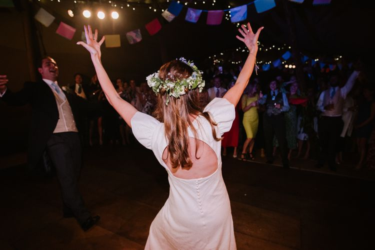 Bride in Open Back Gown From The Mews Bridal with Flower Crown | Bright Festival Themed At Home Wedding in a Tipi | McGivern Photography