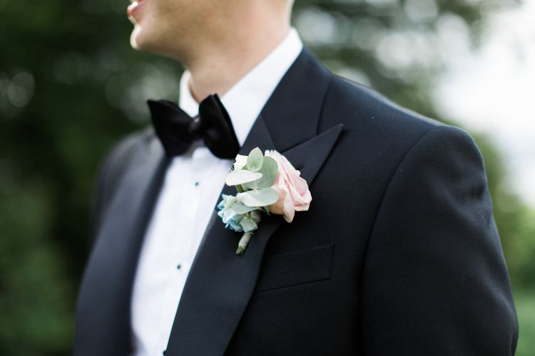 Groom in Chester Barrie Black Tie Suit with Pastel Buttonhole