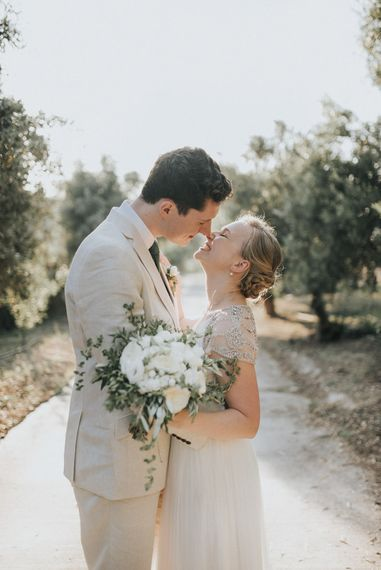 Bride in Catherine Deane Gown | Groom in Beige Austin Reed Suit | Outdoor Pastel Destination Wedding at Agreco in Greece | Best Moments Wedding Planner | Paulina Weddings Photography