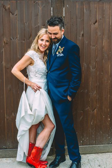 Bride in Red Cowboy Boots and Ivy & Aster Secret Garden Wedding Dress | Groom in Navy Reiss Suit | Rustic Wedding at Yoghurt Rooms in Sussex | Louise Griffin Photography
