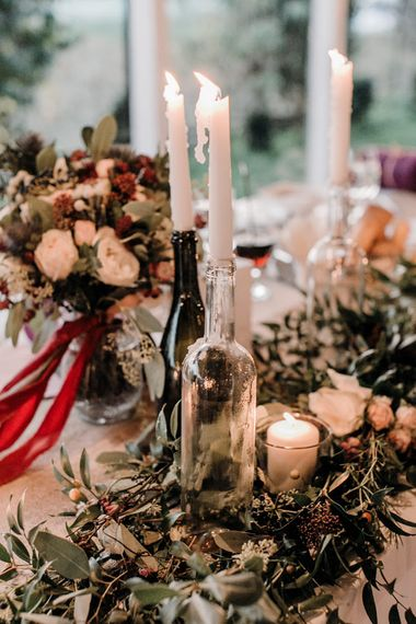 Wedding Reception Centrepieces with Greenery Table Runners & Tappered Candles in Bottles
