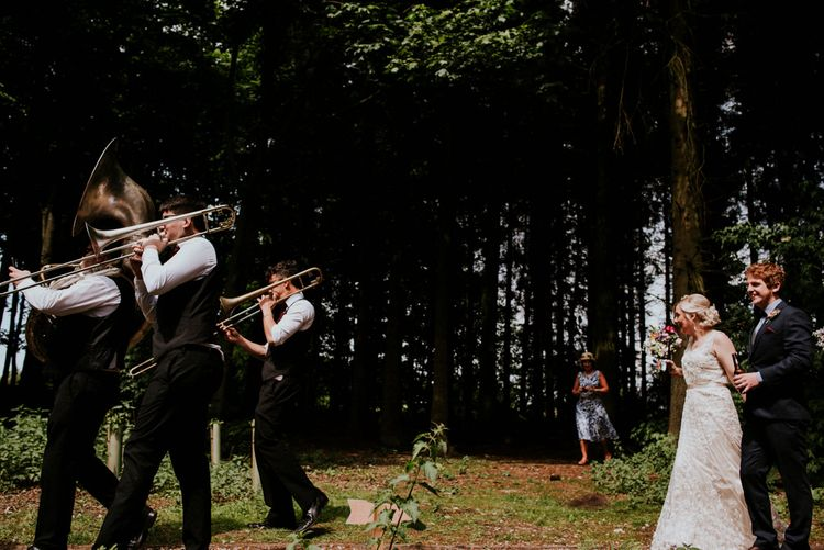 Brass Band Procession   Bride in Catherine Deane Gown   Groom in Ben Sherman Suit, Bow Tie & Gingham Shirt   Colourful Outdoor Wedding at Lineham Farm in Leeds   Shutter Go Click Photography