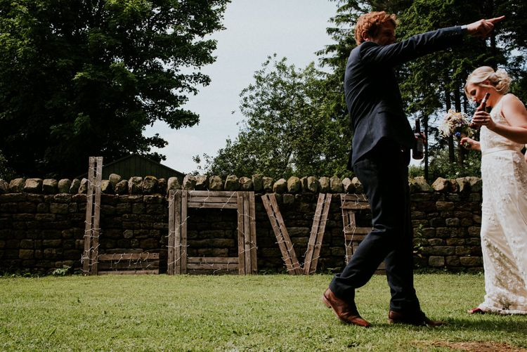 Wood LOVE Sign wrapped in Fairy Lights   Wedding Decor   Colourful Outdoor Wedding at Lineham Farm in Leeds   Shutter Go Click Photography