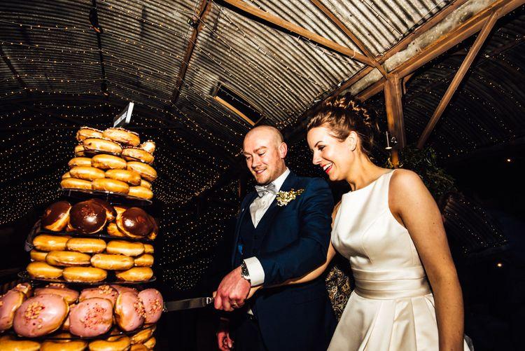 Bride & Groom Cutting the Krispy Kreme Doughnut Tower Wedding Cake | Michelle Wood Photography