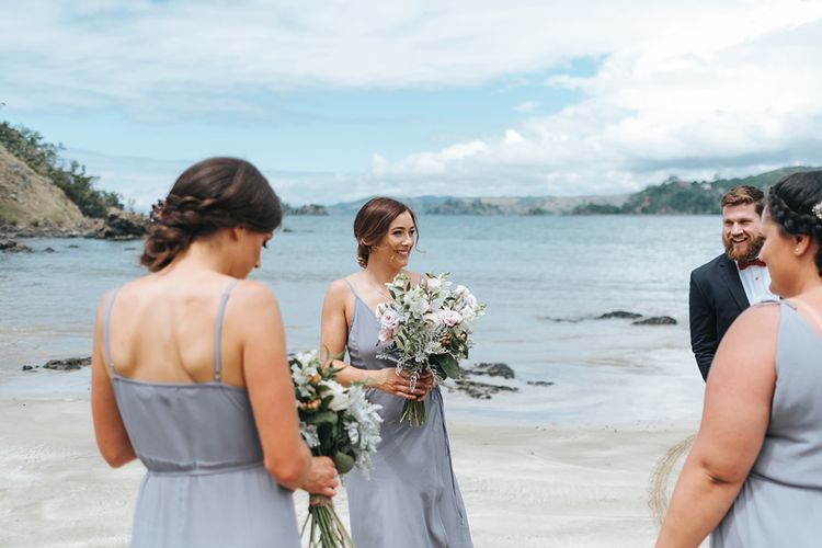 Bridesmaids in Powder Blue Evolution Clothing Dresses | Outdoor Coastal Wedding at Ohawini Bay in New Zealand with Natural Garden Party Reception | Miss Gen Photography