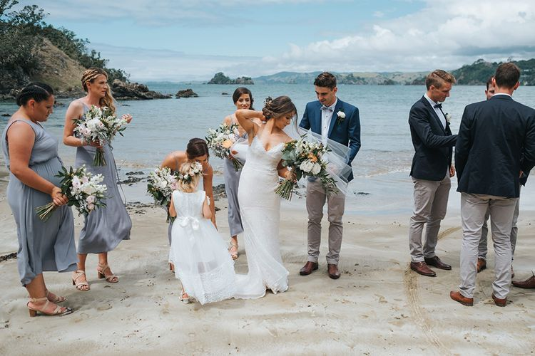 Wedding Party | Bride in Estelle Sally Eagle Gown | Bridesmaids in Powder Blue Evolution Clothing Dresses | Groomsmen in Chinos & Blazers | Outdoor Coastal Wedding at Ohawini Bay in New Zealand with Natural Garden Party Reception | Miss Gen Photography