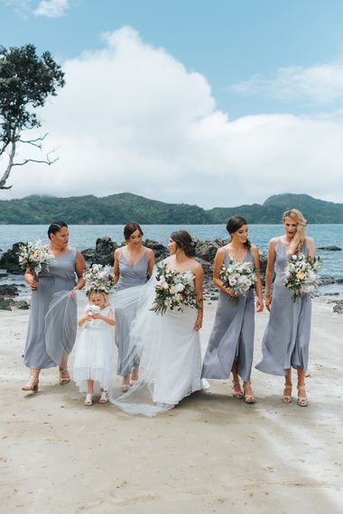Bridal Party | Bride in Estelle Sally Eagle Gown | Bridesmaids in Powder Blue Evolution Clothing Dresses | Outdoor Coastal Wedding at Ohawini Bay in New Zealand with Natural Garden Party Reception | Miss Gen Photography
