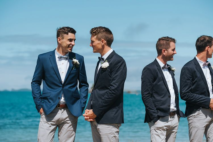 Wedding Ceremony | Groomsmen in Grey Chinos & Navy Blazers | Outdoor Coastal Wedding at Ohawini Bay in New Zealand with Natural Garden Party Reception | Miss Gen Photography