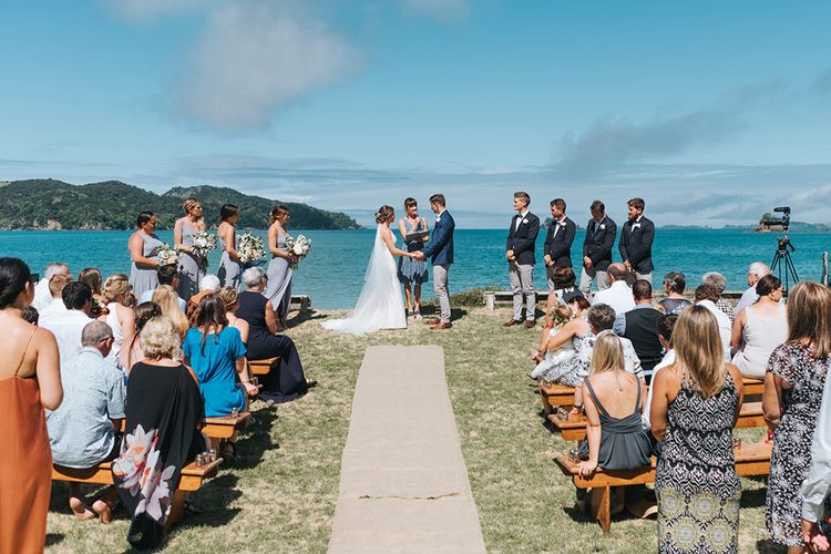 Wedding Ceremony | Bride in Estelle Sally Eagle Gown | Grooms in Grey Chinos & Navy Blazer | Outdoor Coastal Wedding at Ohawini Bay in New Zealand with Natural Garden Party Reception | Miss Gen Photography