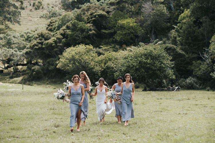 Wedding Party | Bride in Estelle Sally Eagle Gown | Bridesmaids in Powder Blue Evolution Clothing Dresses | Groomsmen in Grey Chinos & Navy Blazers | Outdoor Coastal Wedding at Ohawini Bay in New Zealand with Natural Garden Party Reception | Miss Gen Photography