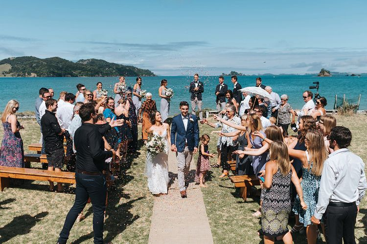 Wedding Ceremony | Bride in Estelle Sally Eagle Gown | Groom in Chinos & Blazer | Outdoor Coastal Wedding at Ohawini Bay in New Zealand with Natural Garden Party Reception | Miss Gen Photography