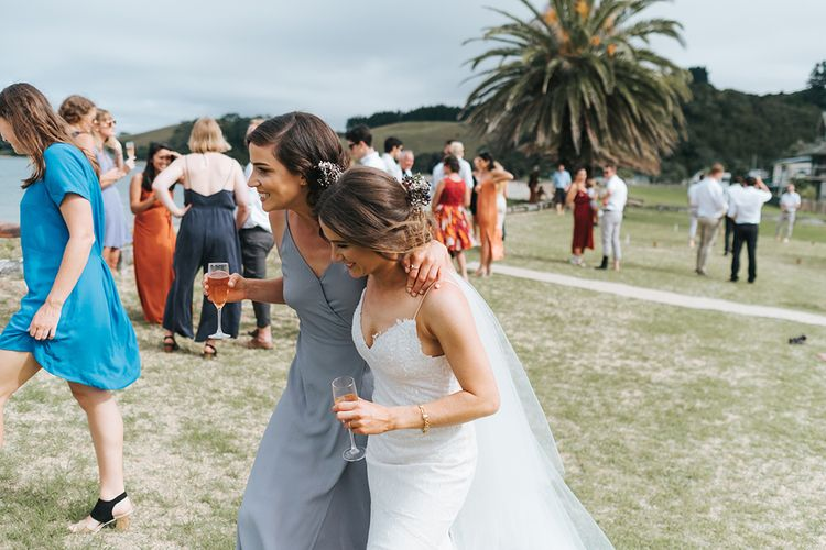 Bride in Estelle Sally Eagle Gown | Bridesmaid in Powder Blue Dress | Outdoor Coastal Wedding at Ohawini Bay in New Zealand with Natural Garden Party Reception | Miss Gen Photography