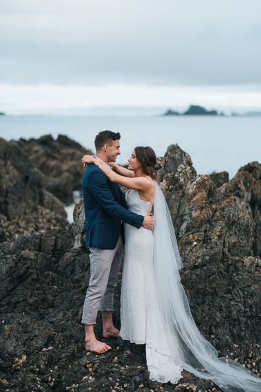 Bride in Estelle Sally Eagle Gown | Groom in Chinos & Blazer | Outdoor Coastal Wedding at Ohawini Bay in New Zealand with Natural Garden Party Reception | Miss Gen Photography