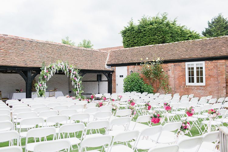 Outdoor Wedding Ceremony With White Chairs & Pink Floral Chairbacks