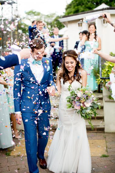 Bride in Pronovias Gown & Groom Navy in Kin by John Lewis Suit Confetti Moment