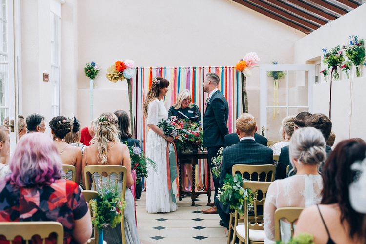 Wedding Ceremony | Ribbon Altar Decor | Bride in Needle & Thread Bridal Skirt | Groom in Check Slaters Suit | Colourful Wedding at Kelmarsh Hall in Northamptonshire | Casey Avenue Photography