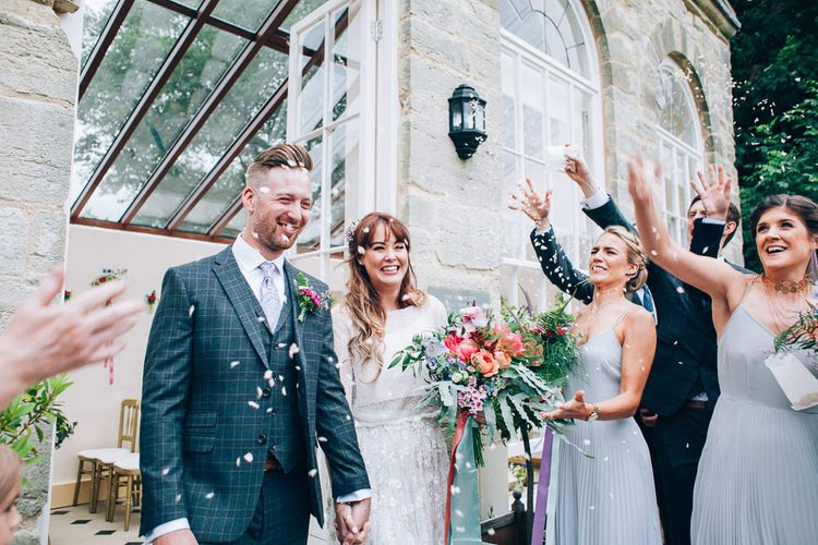 Confetti Exit | Bride in Needle & Thread Bridal Skirt | Groom in Check Slaters Suit | Colourful Wedding at Kelmarsh Hall in Northamptonshire | Casey Avenue Photography