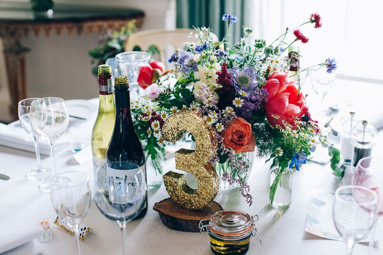 Wild Flower Centrepiece & Gold Glitter Table Number | Colourful Wedding at Kelmarsh Hall in Northamptonshire | Casey Avenue Photography