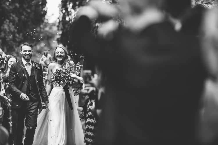 Confetti Exit | Bride in Catherine Deane Carly Bridal Gown | Groom in Navy Suit | Bright At Home Tipi Wedding | Barney Walters Photography