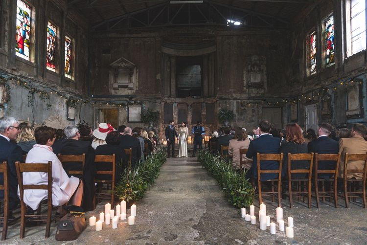 Wedding Ceremony | Candle Light & Greenery Aisle | Bride in Story of My Dress Bridal Gown | Groom in Navy Suit from Tom James Tailors | Vintage Wedding at The Asylum & Town hall Hotel London | Kevin Fern Photography