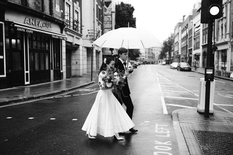 Elegant Bride in Delphine Manivet Prospere Wedding Dress & Groom in Velvet Jacket & Trousers Under an Umbrella