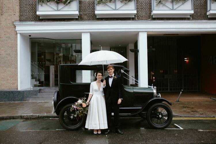 Elegant Bride in Delphine Manivet Prospere Wedding Dress & Groom in Velvet Jacket beside a Vintage Wedding Car