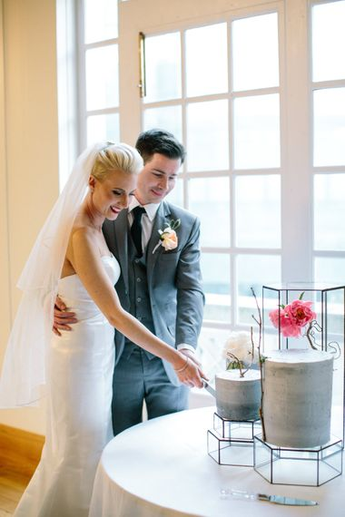 Cutting The Cake   Bride in Anna Sorrano Gown   Groom in Grey Suit   Stylish Hackney Town Hall Wedding   Camilla Arnhold Photography   This Modern Revelry Film