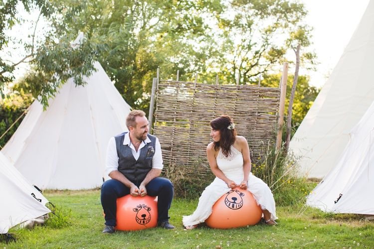 Bride & Groom With Space Hoppers // Festival Inspired DIY Wedding With Relaxed Dress Code Hay Bale Seating For Ceremony And Garden Games With Images From Livvy Hukins Photography