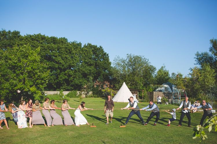 Tug Of War Garden Game For Wedding // Festival Inspired DIY Wedding With Relaxed Dress Code Hay Bale Seating For Ceremony And Garden Games With Images From Livvy Hukins Photography