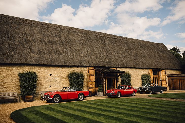 Red Vintage Cars Outside The Tythe Barn in Oxfordshire