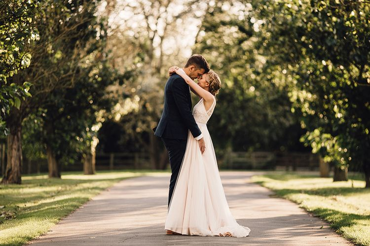 Bride in Catherine Deane Tamsin Wedding Dress & Groom in Paul Smith Suit