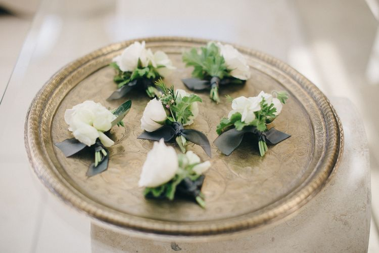 Buttonholes on Gold Platter | M and J Photography