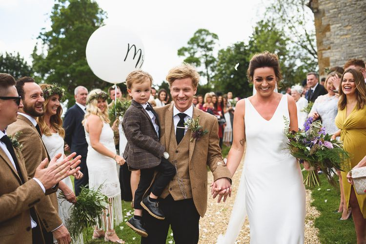 Confetti Exit | Bride in Charlie Brear Gown | Groom in Navy & Mustard Suit | Outdoor Tipi Wedding at The Georgian Rectory Buckingham | Jackson & Co Photography | Blooming Lovely Films