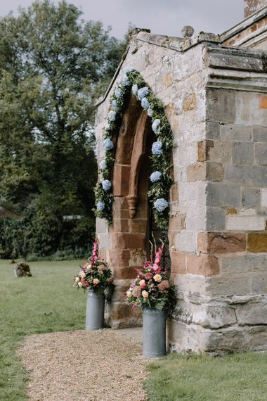 Church Floral Arch Entrance | Rural Wedding in a Sailcloth Tent on Stanford Hall Estate, Northamptonshire | Rebecca Goddard Photography